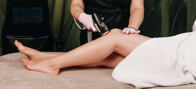 Leg epilation session with laser using modern apparatus to a young woman at the spa center