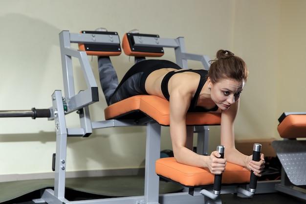 脚のエクササイズ-ジムでマシンを使って脚をやっている若い女性