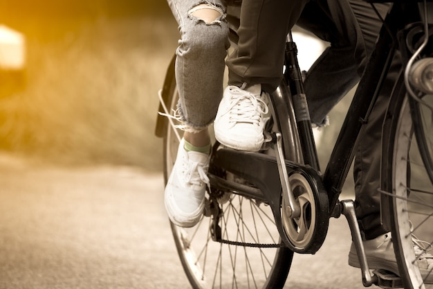 Leg and feet of young couple riding a bicycle together
