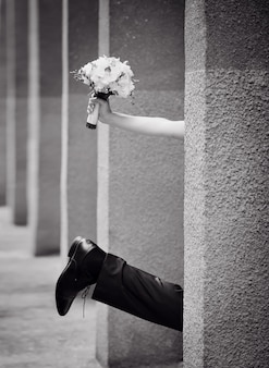 Leg of the groom and hand of the bride with a bouquet