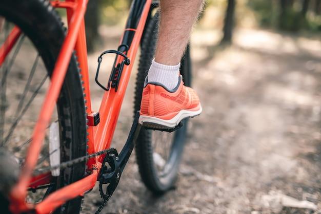 Нога в кроссовке на педали велосипеда во время езды на открытом воздухе