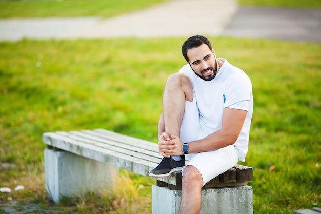 足の怪我。屋外で運動中に足の痛みに苦しんでいる男性アスリート。