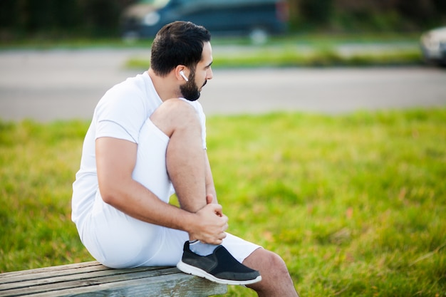 Leg injury. male athlete suffering from pain in leg while exercising outdoors