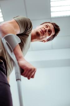 Травма ноги. симпатичный молодой человек с травмой ноги на костылях для ходьбы