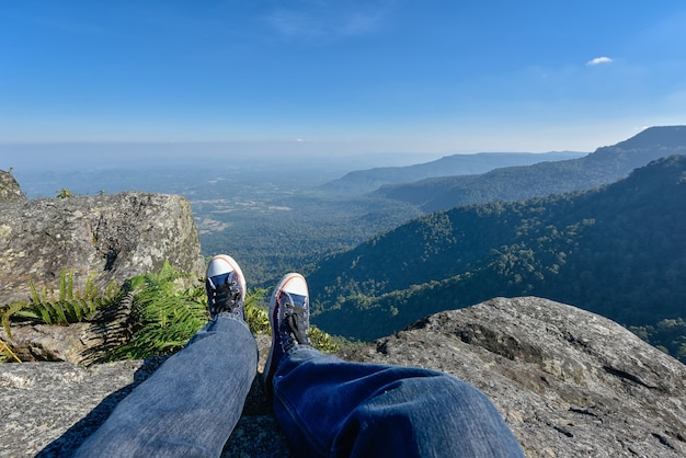 Leg of a man sitting on the edge of a cliff at the mountains, hiker relaxing on cliff