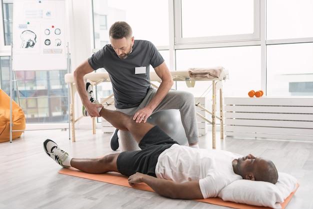 Мышцы ног. умный умелый тренер держит ногу пациента во время специального реабилитационного упражнения