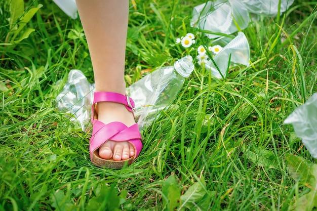 Нога маленькой девочки топчет пластиковую бутылку