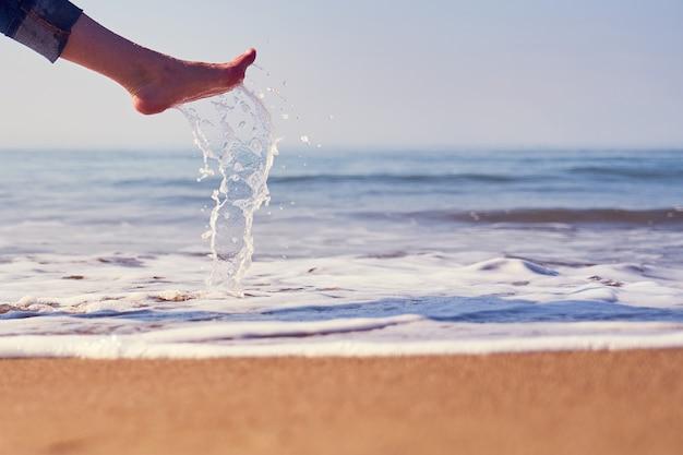 波と地平線と熱帯の砂浜で動きの女性の脚