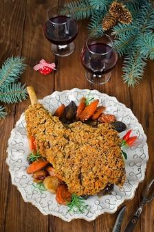 スパイシーなパンの皮で焼いた子羊の脚。丸皿にロースト野菜を添えた子羊のロースト脚