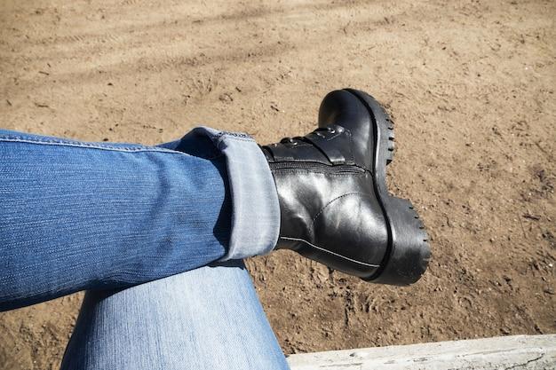 파란색에서 벤치 사람에 앉아 다리는 청바지와 검은 부팅을 겹쳐서.