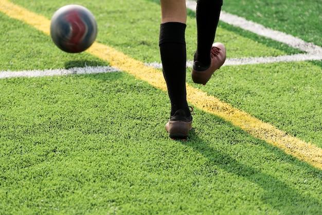 Нога футболиста тренировки на зеленом футбольном поле