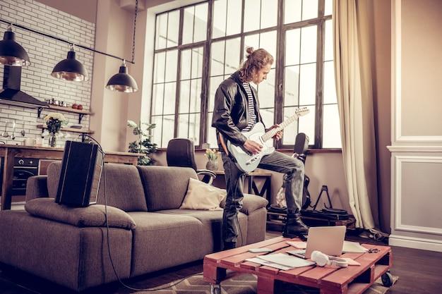 テーブルの上の脚。ロックソングを演奏しながらテーブルに足を置く巻き毛のスタイリッシュなミュージシャン