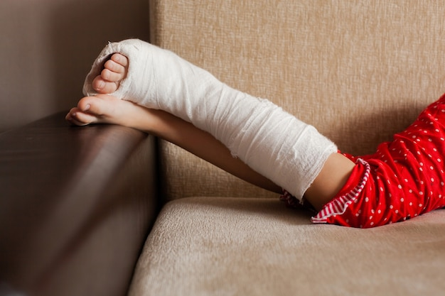 Leg in plaster of a teenage girl on a sofa after an accidental fall with an ankle fracture