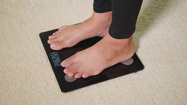 Шагая ногой стоя на напольных электрических весах