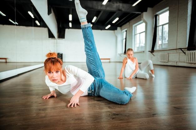 レッグスイング。ブルージーンズを履いて脚振りをするプロのバレエ教師