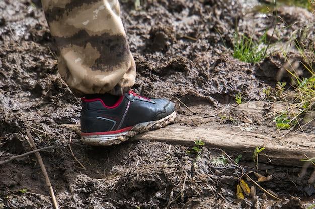 スニーカーを履いたレッグツーリストが泥の中を歩く