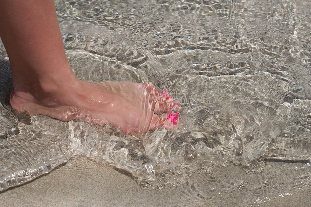 Leg of a white caucasian woman on a tropical elafonissi beach with colorful sand in crete greece.