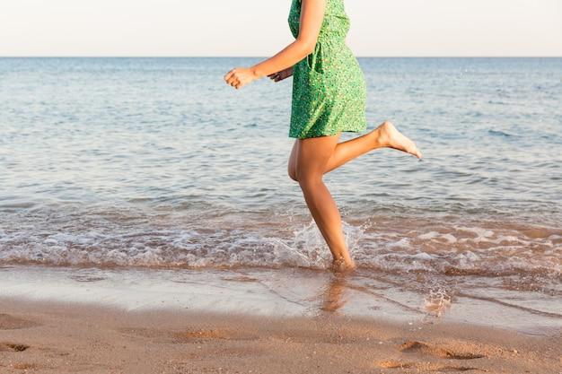 Leg of woman running on beach with water splashing.
