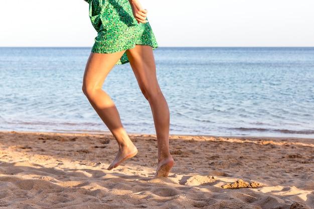 Leg of woman running on sand beach. summer vacation. happy beautiful woman running on the beach