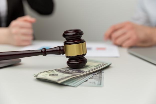 Понятие юридических алиментов. взгляд крупного плана деревянного молотка и денег.