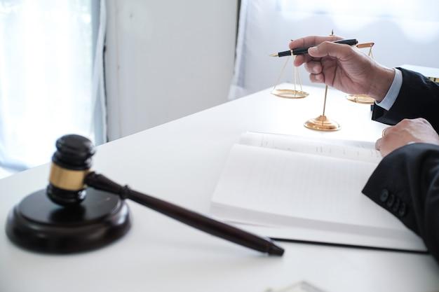 법률 고문은 망치 및 법률 법률과 서명한 계약을 고객에게 제시합니다. 정의와 변호사 개념입니다.