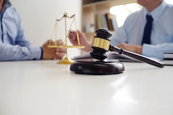 Legal counsel presents to the client a signed contract with gavel and legal law