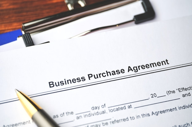 Legal document business purchase agreement on paper close up.