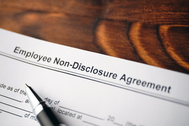 Legal document employee non-disclosure agreement on paper close up.