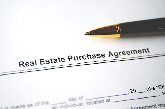 Legal document real estate purchase agreement on paper close up.