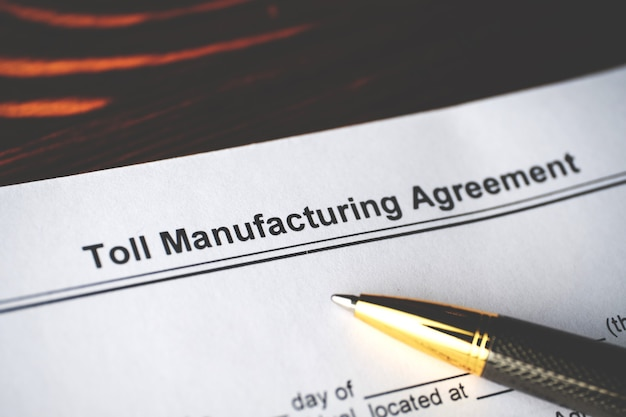 Legal document toll manufacturing agreement on paper close up.
