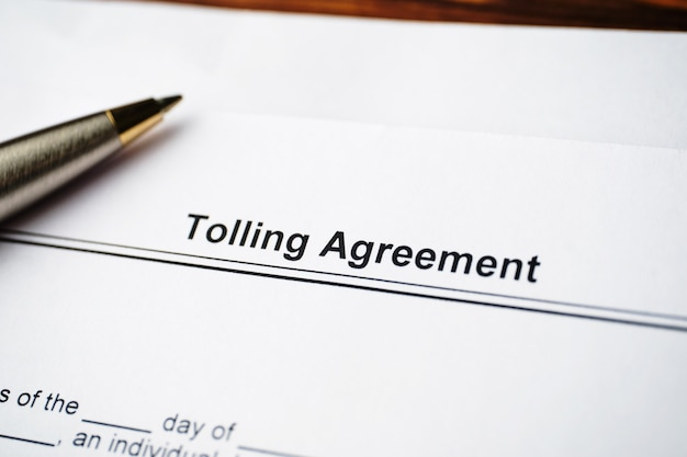 Legal document tolling agreement on paper close up.