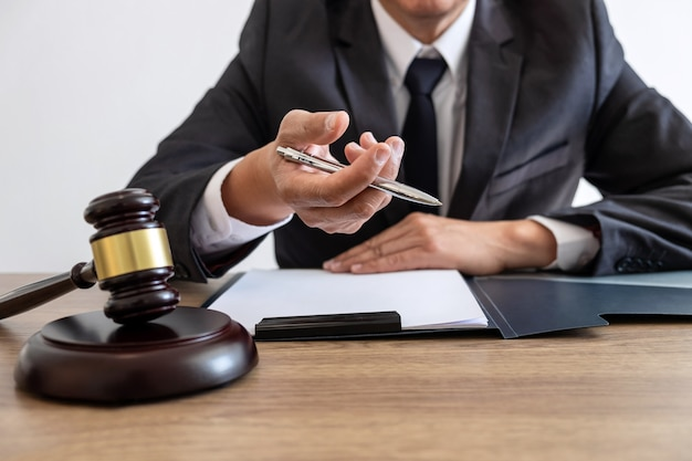 Legal law, advice and justice concept, counselor lawyer or notary working on a documents and report of the important case and wooden gavel, brass scale on table in courtroom