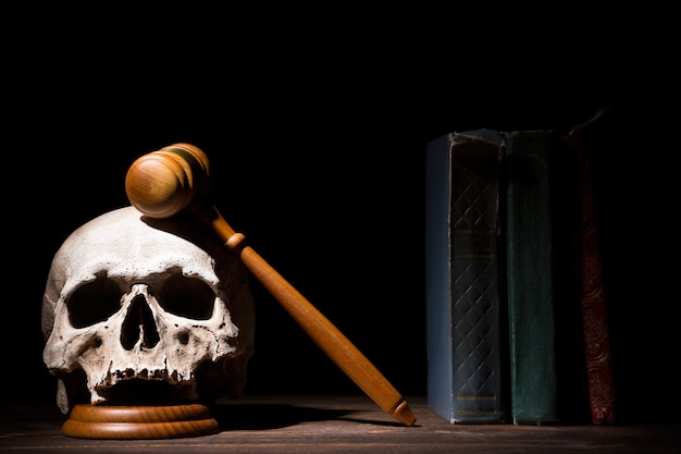 Legal law, justice and murderment concept. wooden judge gavel hammer on human skull near books against black background.