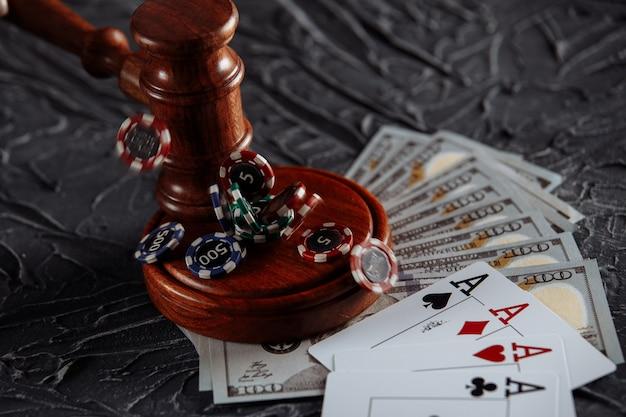 온라인 도박 개념에 대한 법적 규칙. 나무 망치와 회색 배경에 카드 놀이입니다.