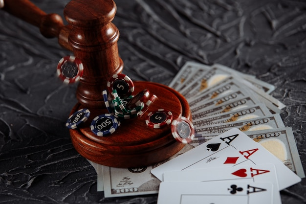 Legal rules for online gambling concept. wooden gavel and playing cards on grey background.