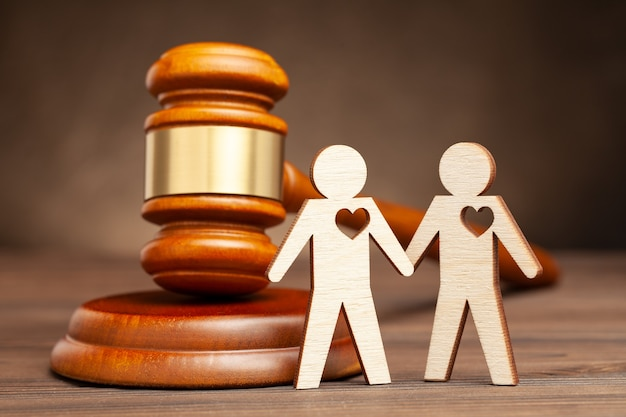 同性結婚を合法化。裁判官のハンマーの手を握っている2人のゲイの男性。同性の人々の法律と結婚。