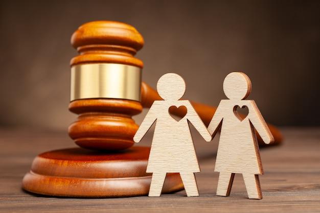 Узаконенный однополый брак. две лесбиянки фигуры с судьей молотком. закон и брак однополых людей.