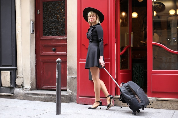 Leggy blonde in a short black dress with a hat and a suitcase is walking down the street in paris