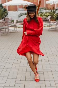 レストランのテラスで陽気に踊る脚の長い茶色の髪の女性。新しいスナップショットを楽しんでいる優れたスタイルのモデル