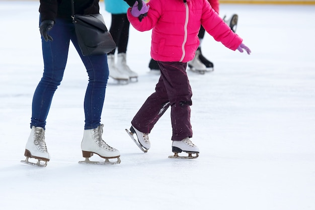 The legs of an adult and child skating on the ice rink