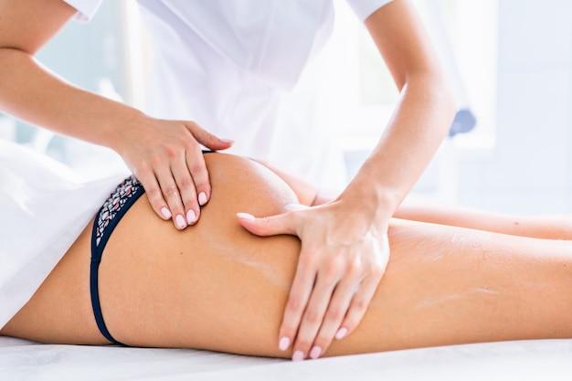 다리와 엉덩이 마사지를 통해 셀룰 라이트를 줄이고 건강한 모습을 유지합니다. 클라이언트 피부에 크림을 적용하는 여자의 손.