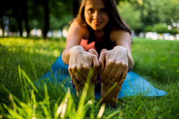 Ноги и руки девушки крупным планом, занимающейся пилатесом на коврике в парке