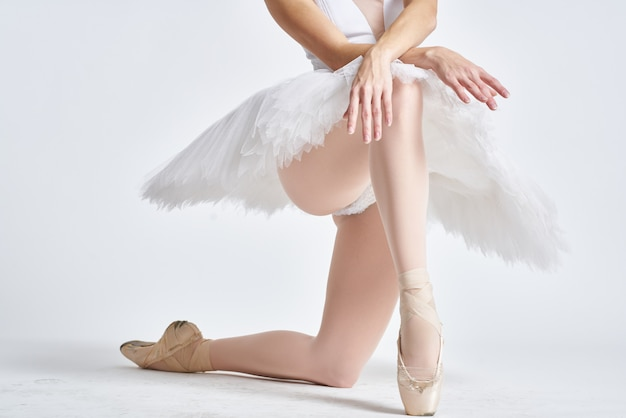 Legs of a ballerina in pointe shoes on a light