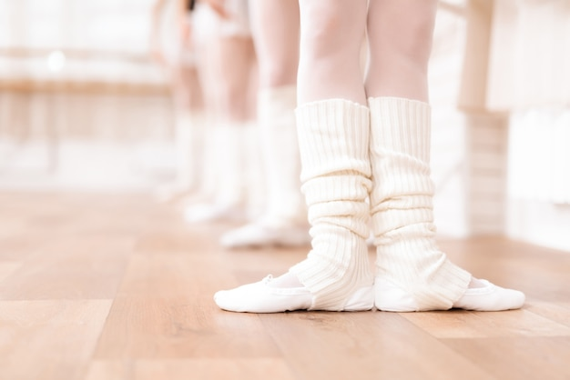 The legs of ballerinas are training on the floor.