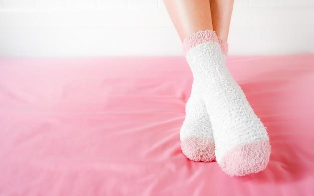 Legs of a beautiful women are wearing warm socks on bedroom.
