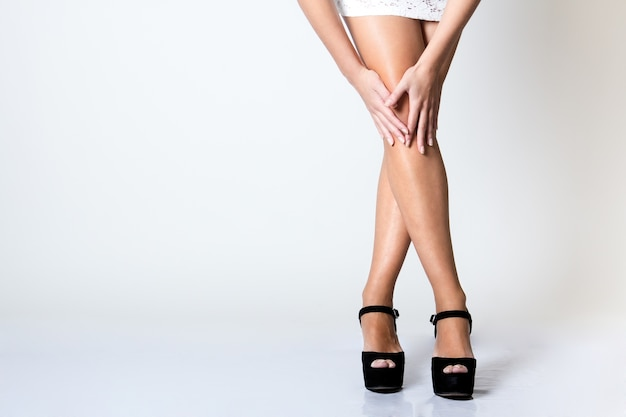 Legs of  beautiful young woman posing with white screen