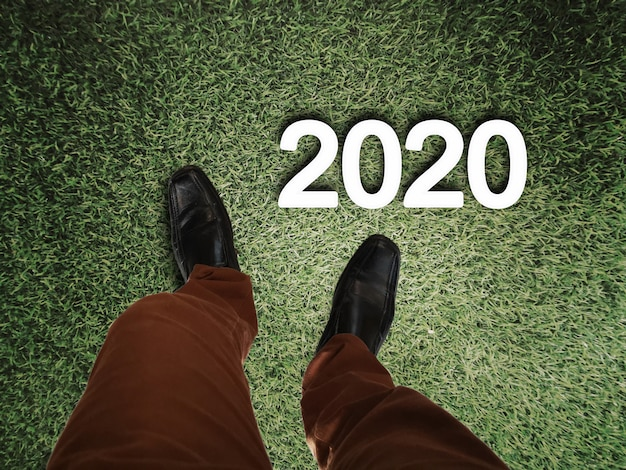 Legs of business man standing on grass floor with 2020