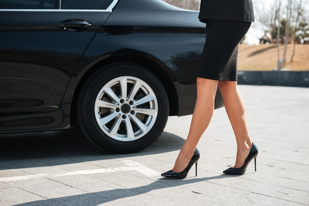 Legs of businesswoman with high heels shoes walking near car