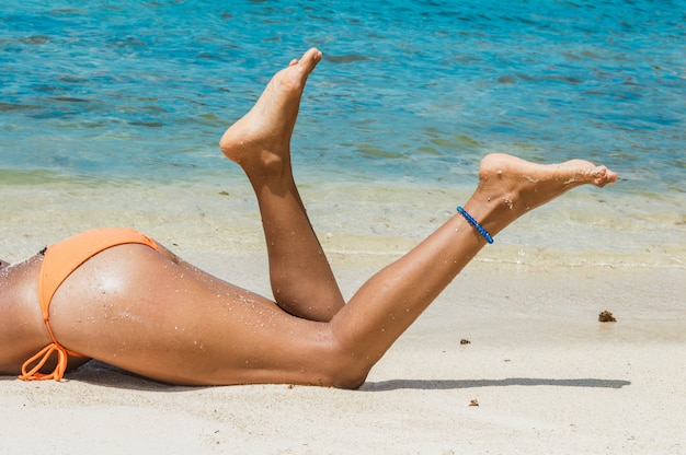 Legs and buttocks of woman lying on her stomach on the sand. closeup of female model legs lying on the shore of the beach.