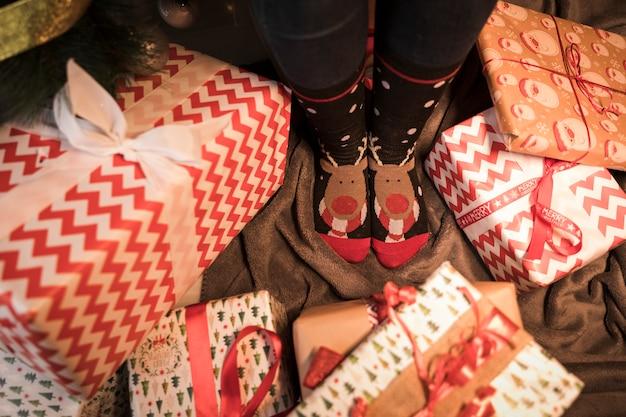 Legs in christmas socks between present boxes